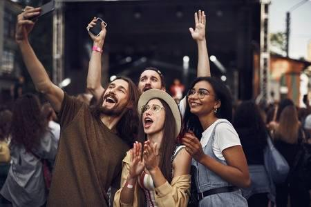 110952958-having-fun-waist-up-portrait-of-young-people-taking-photo-with-smartphone-while-enjoying-concert
